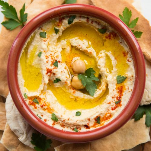 Bowl of hummus garnished with olive oil and paprika