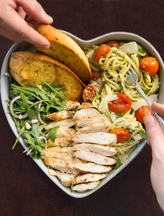 over head shot of pasta served in heart shaped bowls with two hands and forks digging in