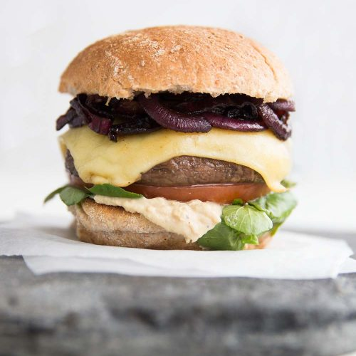 Portobello Mushroom Burger with caramelised onions, cheese, hummus, tomato and watercress