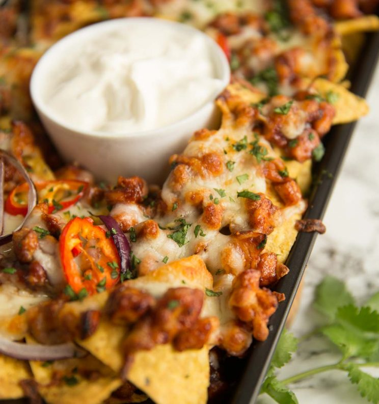 BBq chicken nachos fresh out the oven served with pot of sour cream on the centre
