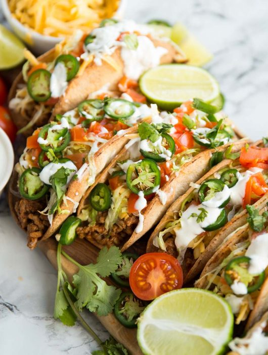 Beef tacos on a wooden board covered in garnishes such as lime, coriander and tomatoes
