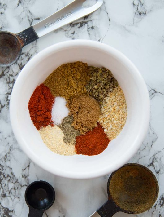 Small bowl with taco seasoning surrounded by measuring spoons