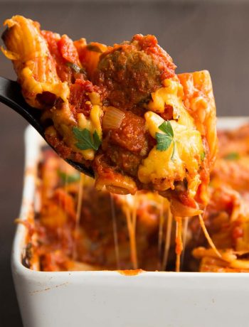 Scopping out meatball and pasta with cheese pouring down spoon