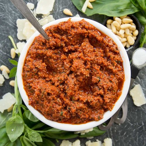 Bowl of Sun Dried Tomato Pesto with spoon poking out surrounded by basil, pinenuts and parmesan