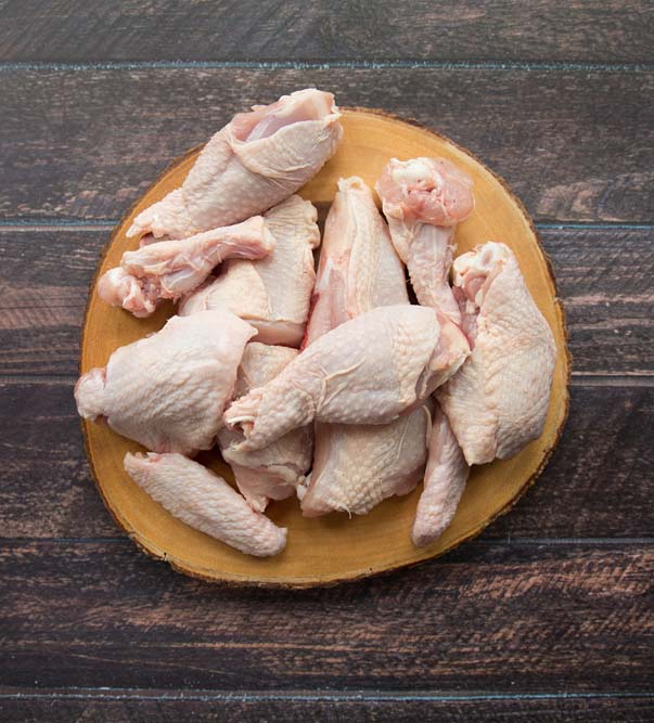 Whole chicken cut into 12 pieces on a wooden board