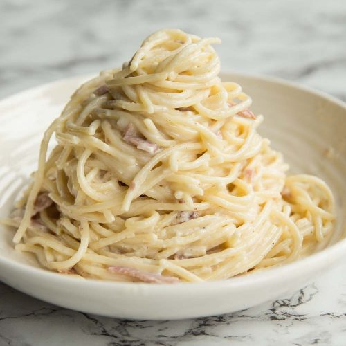 Cream Cheese Pasta served on a curved white plate on a marble surface