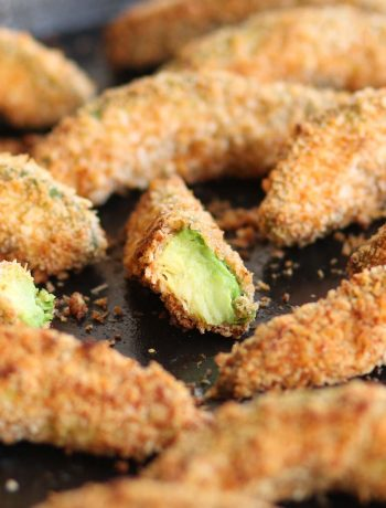 Avocado Fries fresh out the oven with focus on half a fry showing the avocado