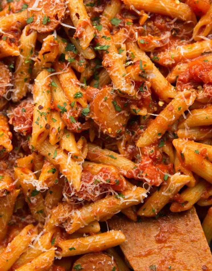 Overhead shot of Arrabiata with Penne and Smoked Sausage in a saucepan garnished with parmesan, chilli flakes and parsley