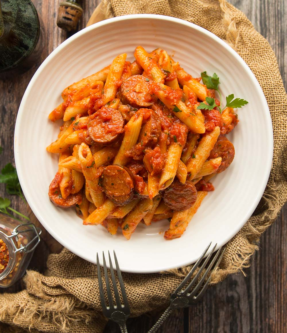 Penne Arrabiata with Smoked Sausage served in a white bowl with two fork on a wooden background