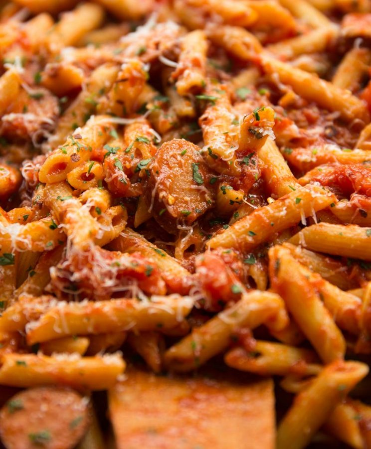 Spicy Arrabiata Penne with Smoked Sausage in a saucepan wit extra chilli flakes on top
