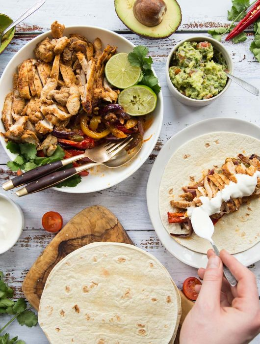 Flat lay of chicken fajitas with sides and garnish including sour cream and guac