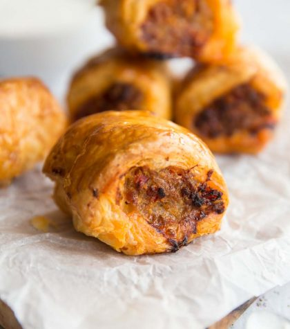 Pork and Chorizo Sausage Roll on baking paper with 4 in the background