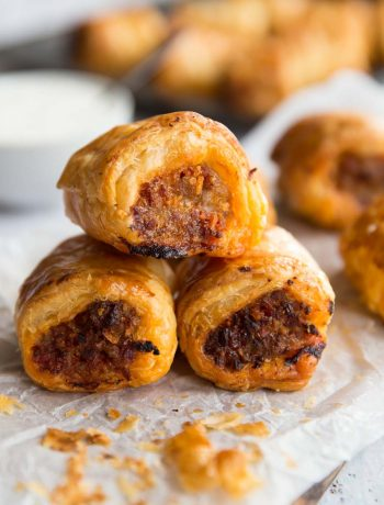 3 Chorizo Sausage Rolls stacked on top of each other with dip and other sausage rolls in the background