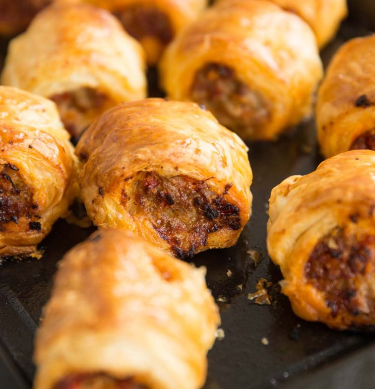closeup of chorizo sausage rolls fresh out the oven on black baking tray