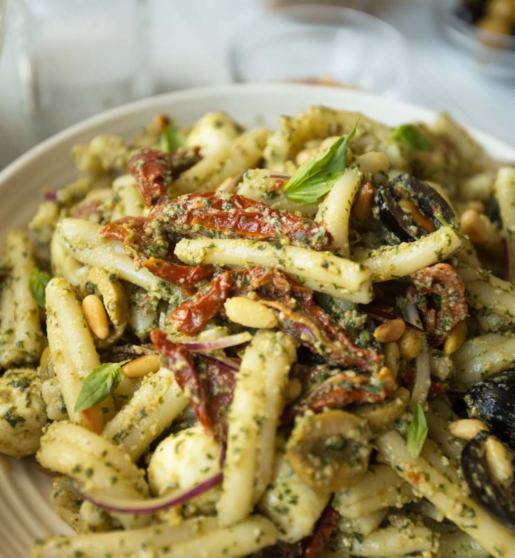 Close up shot of pesto pasta salad with focus on sun dried tomato
