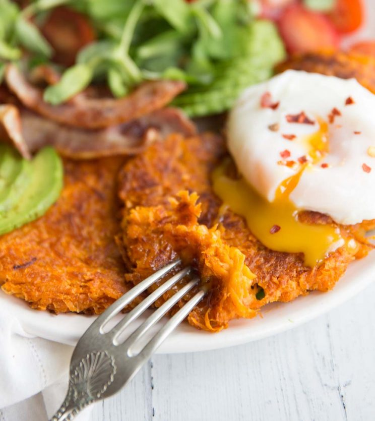 Sweet potato hash brown patties on a white plate with a poached egg on top and a side salad in the background. yolk pouring out of the egg on to the hash browns