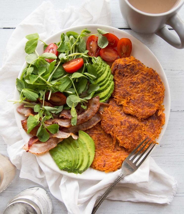 Sweet Potato Hash Browns on a white place with a side salad, bacon and avocados. Coffee and salt and pepper in the background.