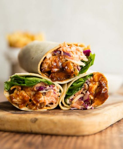 3 bbq chicken wraps stacked on a wooden chopping board with french fries blurred in the background