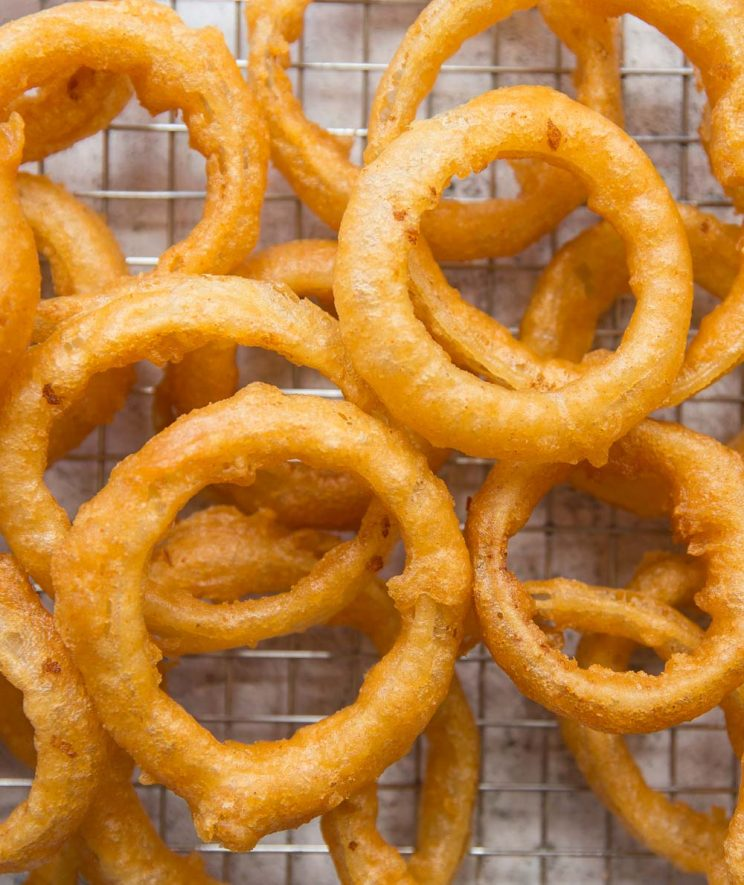 overhead shot of onion rings scattered across a wire rack