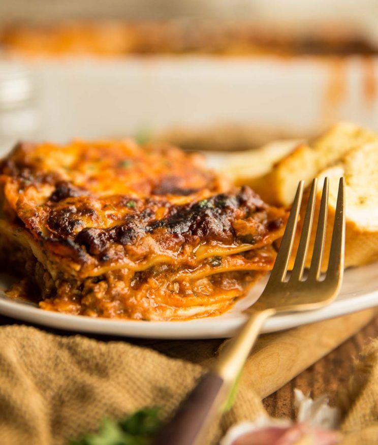 one portion of lasagne served on a plate with baking dish and garlic bread blurred in the background
