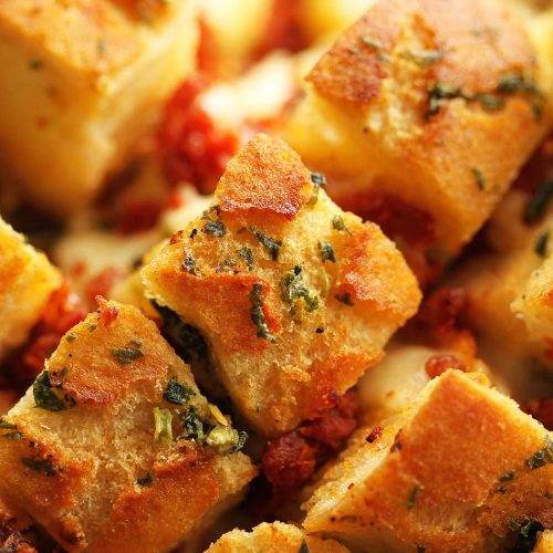 closeup of pull apart bread with focus on finely chopped basil