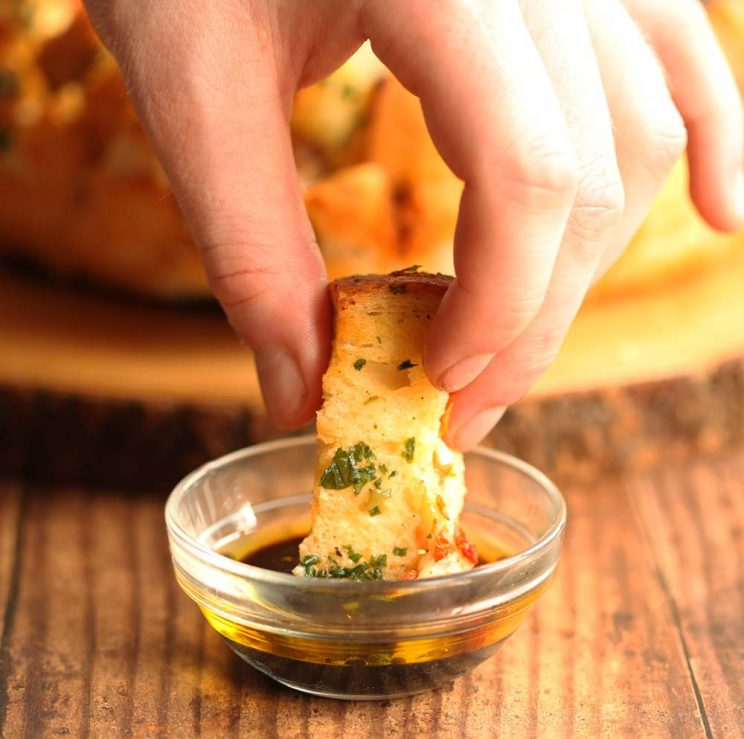 dipping pull apart bread into balsamic and olive oil dip