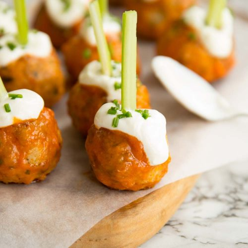 meatballs glazed in buffalo sauce on chopping board with sour cream and chives drizzled on top and celery stuck through the top