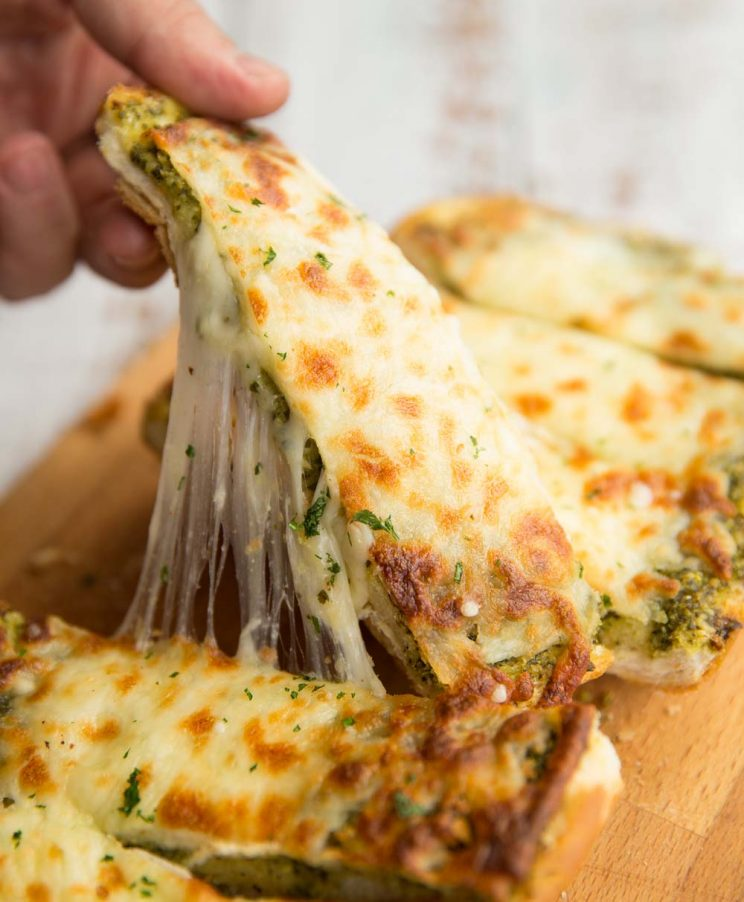 Pull one slice of garlic bread away from loaf with cheese pulling away