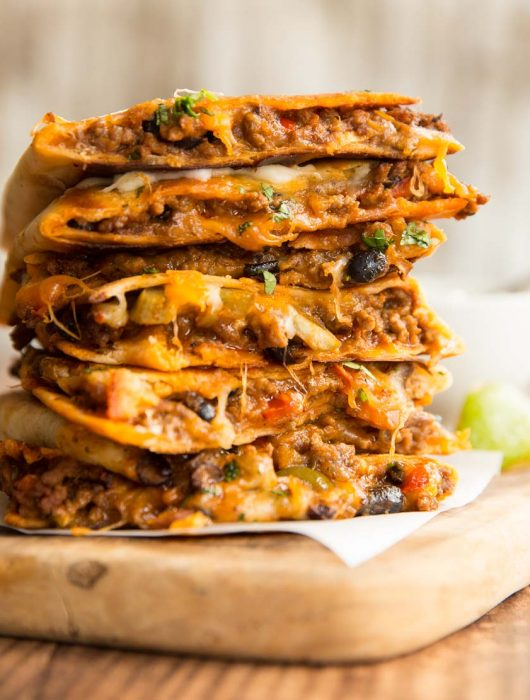 quesadillas stacked on top of each other with filling slightly pouring out
