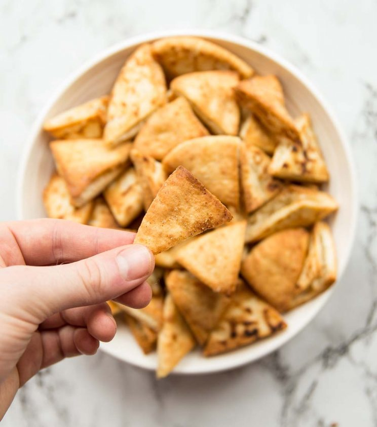 holding a pita chip above a bowl full of pita chips. Focus on holding pita chip.