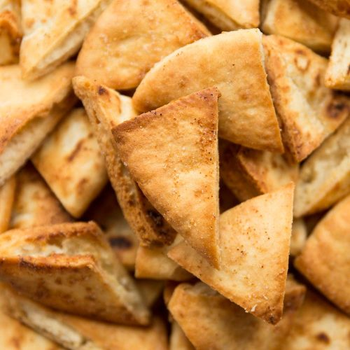 overhead shot of bowl of pita chips, focus on one