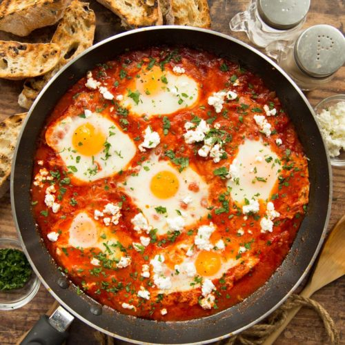 overhead shot of shakshuka in pan surrounded by ciabatta and seasonings