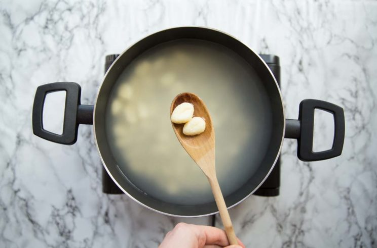 gnocchi in a pot of boiling water, lifting up two pieces on a wooden spoon