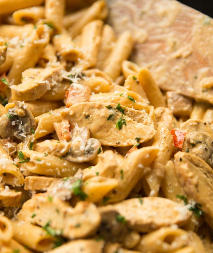 cajun chicken pasta in a skillet with wooden spoon blurred in background