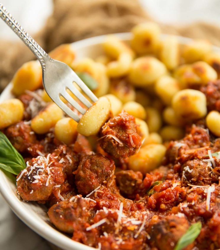 fork holding gnocchi and meatball with a bowl in the background full of gnocchi and meatballs