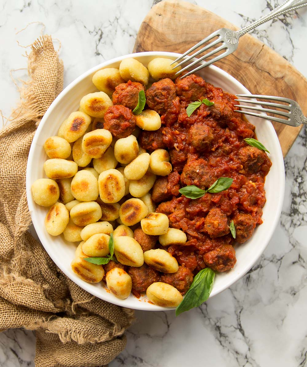 overhead shot of gnocchi and sausage meatballs in white bowl on brown chopping board