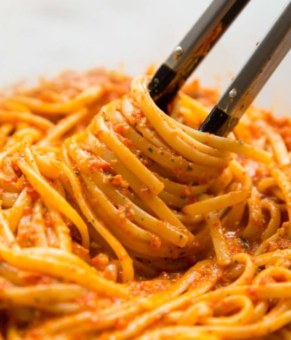 pasta tongs twirling in a bowl of linguine