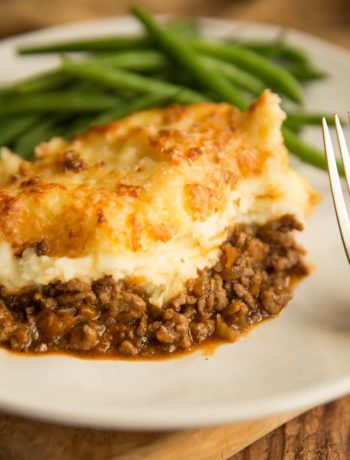 shepherd's pie plated up with green beans blurred in the background