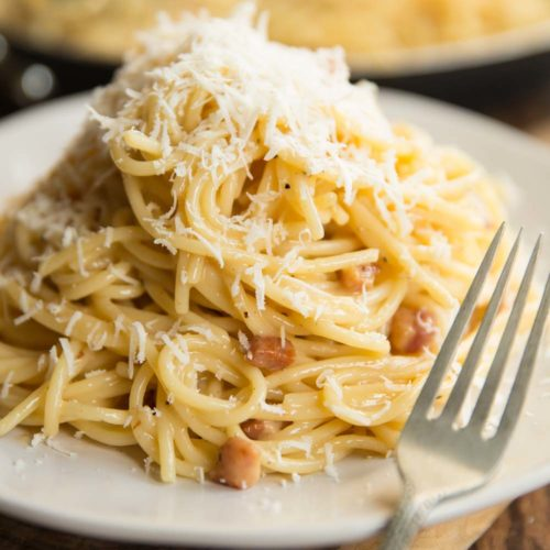 spaghetti carbonara on white plate with saucepan blurred in background and fork resting on plate