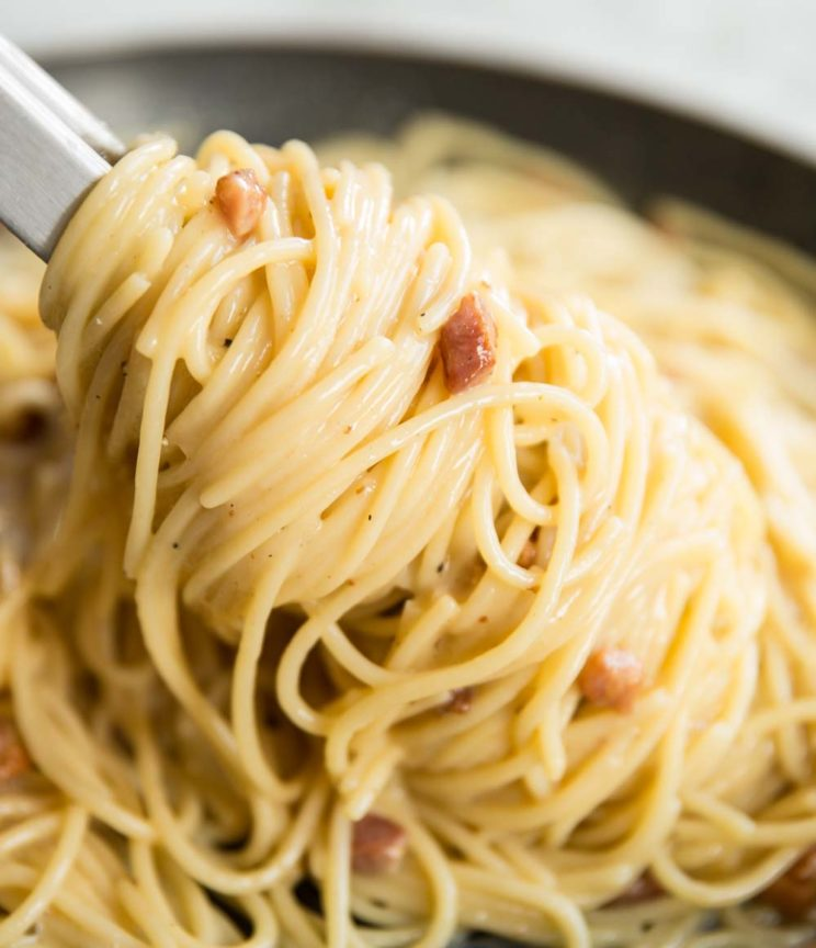 twisting carbonara in a saucepan with pasta tongs