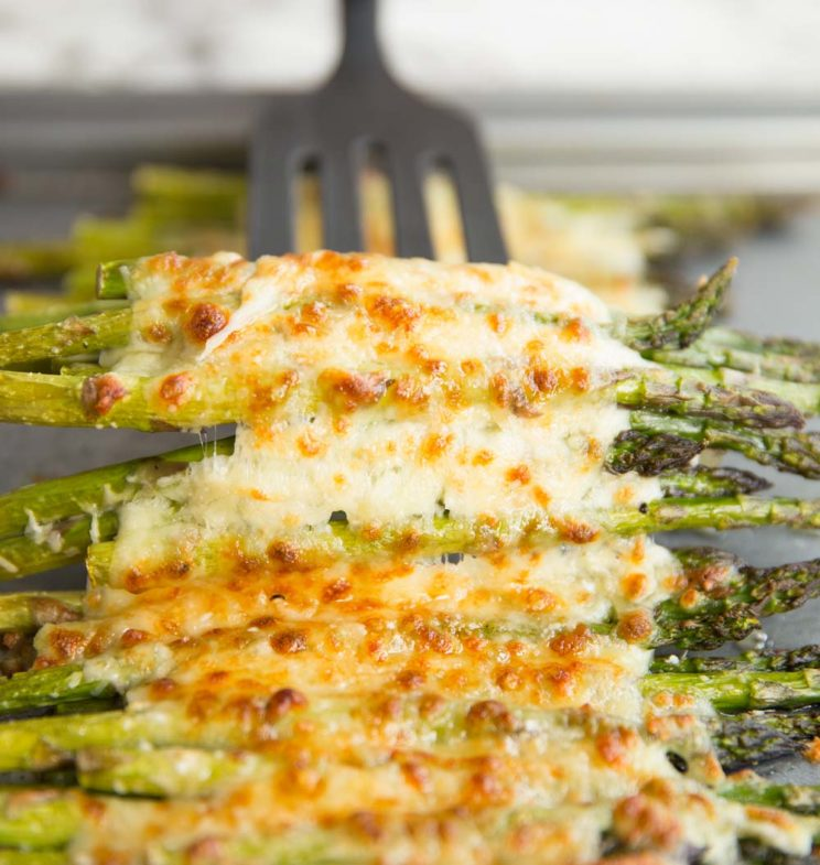 cheesy asparagus on baking tray with spatula ready to pull up from underneath