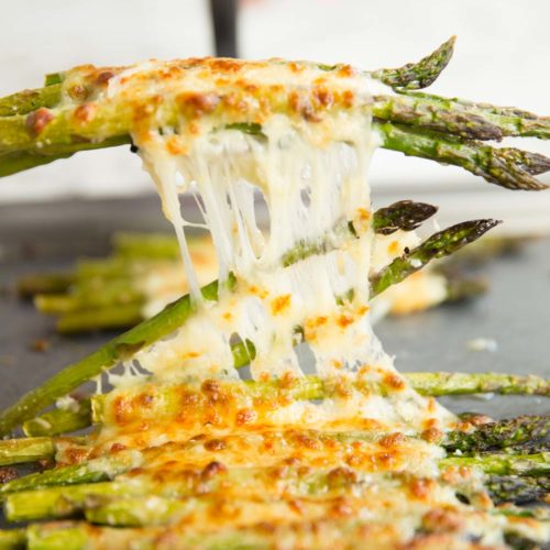 pulling cheesy asparagus off tray with spatula