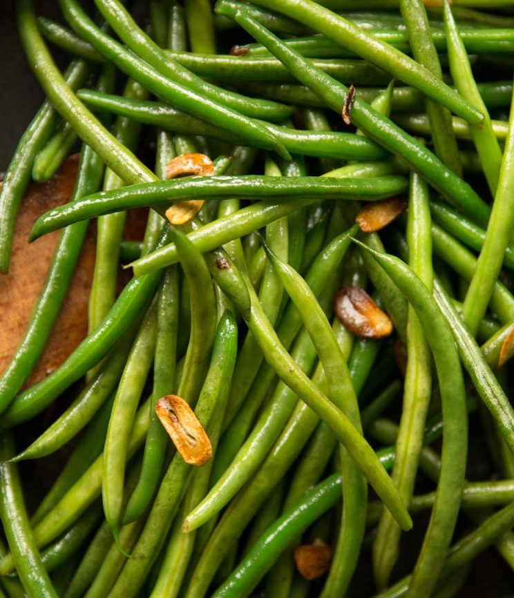overhead shot of green beans in pan with crispy bits of garlic