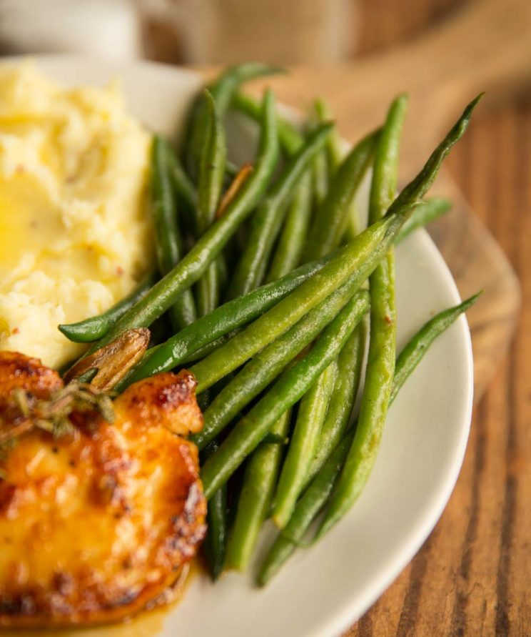 green beans on a plate with chicken and mash