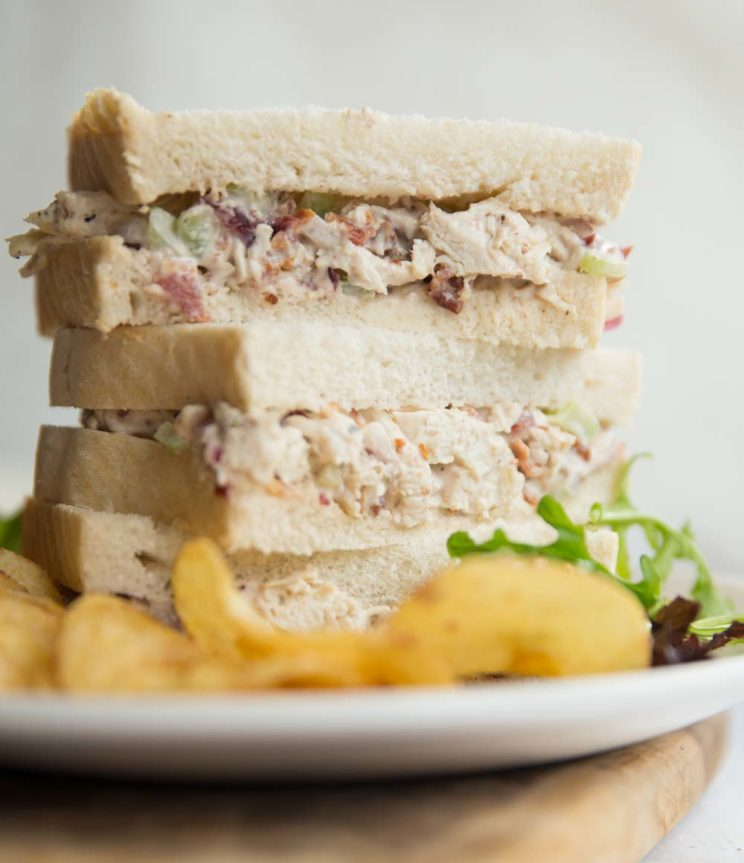 3 half sandwiches stacked on a white plate with crisps and salad leaves