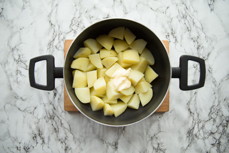 boiled potatoes with butter in black pop on chopping board