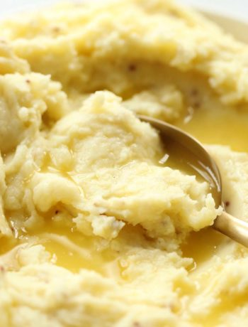 spoon digging into mustard mash with melted butter on top