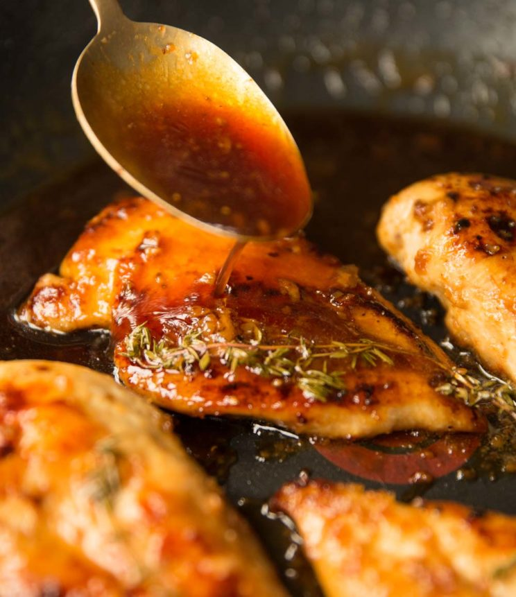 pouring honey garlic sauce on chicken breast in skillet with golden spoon