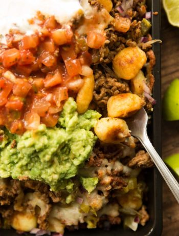 overhead shot of gnocchi nachos in tray with guac, salsa ad sour cream