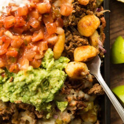 overhead shot of gnocchi nachos in tray with guac, salsa ad sour cream